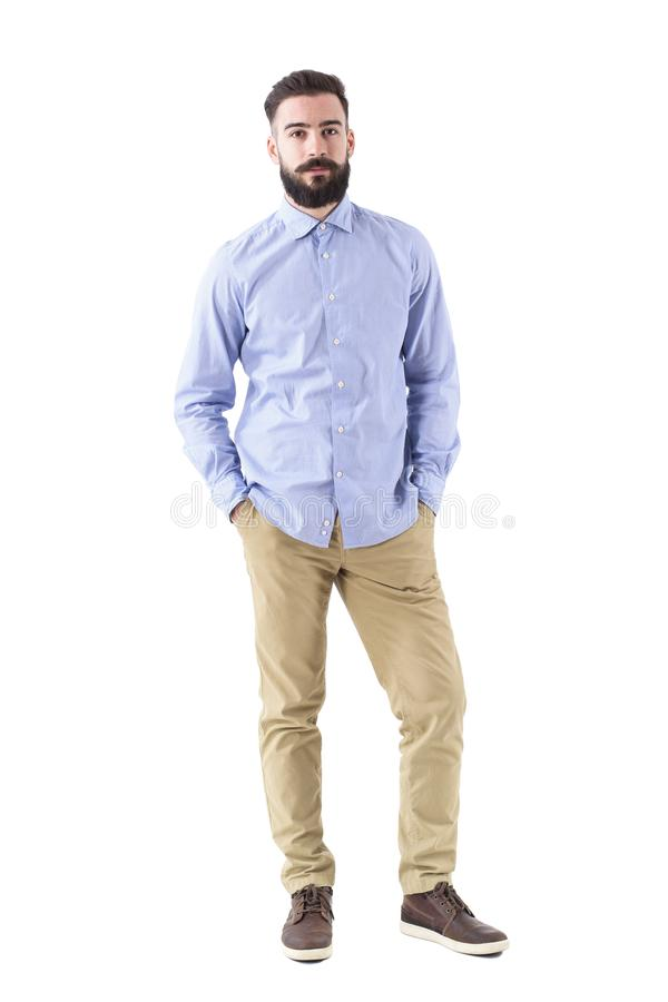 Confident successful serious business man with hands in pockets looking at camera royalty free stock image