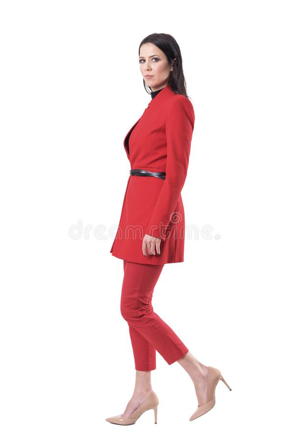 Confident successful serious business woman walking and looking at camera. Side view royalty free stock image