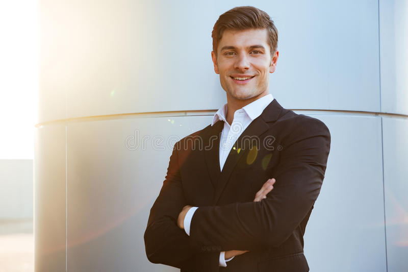 Confident successful young businessman standing with arms crossed stock images
