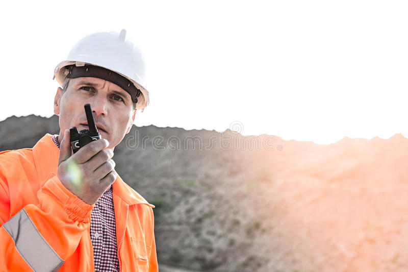 Confident supervisor using walkie-talkie on construction site against clear sky stock images