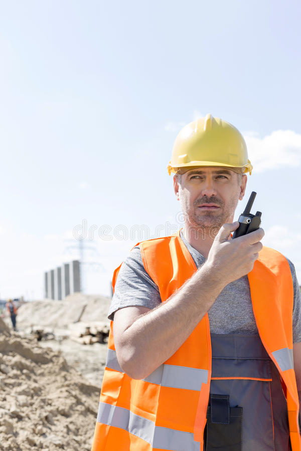 Confident supervisor using walkie-talkie at construction site against sky royalty free stock photos