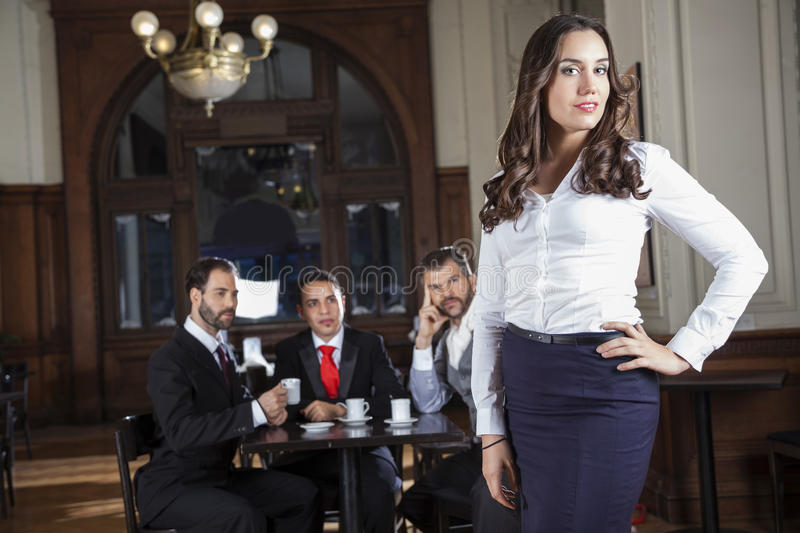 Confident Tango Dancer Standing While Pervert Men Looking At Her. Portrait of confident tango dancer standing while pervert men looking at her in restaurant royalty free stock images