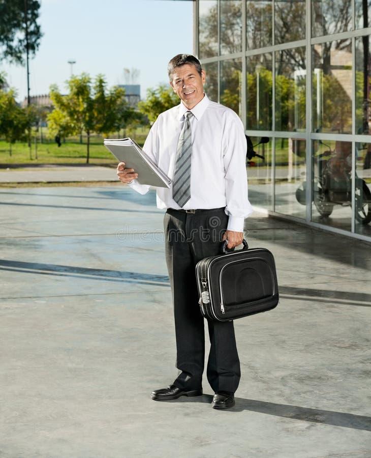 Confident Teacher With Laptop Bag And Books. Full length portrait of confident male teacher with laptop bag and books standing on college stock image