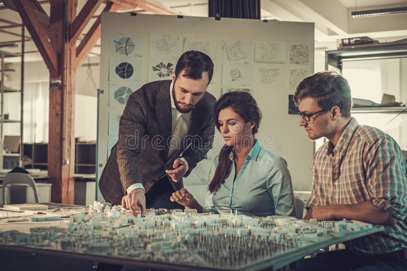 Confident team of engineers working together in a architect studio. royalty free stock photo