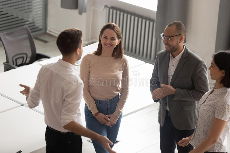 Confident team leader explaining work moments to employees. Top above view mixed race happy coworkers enjoying break time, chatting at modern office. Confident royalty free stock photo