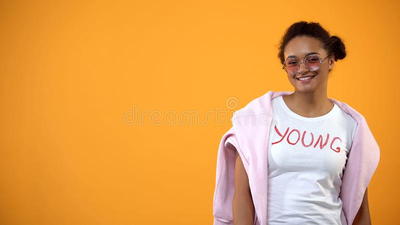 Confident teenage female posing yellow background, courses of fashion and style royalty free stock image