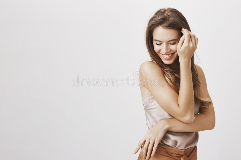 Confident and tender female blushing from compliments. Portrait of flirty sensual feminine woman touching hair near face royalty free stock photography