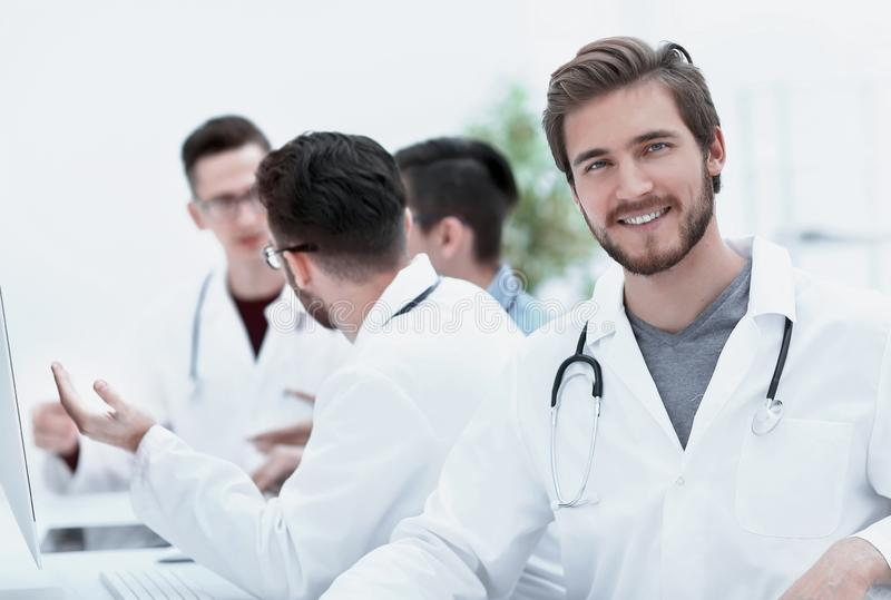 Confident therapist, on the background of his colleagues. Photo with copy space stock image