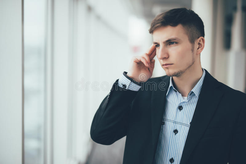 Confident thoughtful businessman in a suit holding hand on chin and looking away while standing with office building in the backgr stock photography