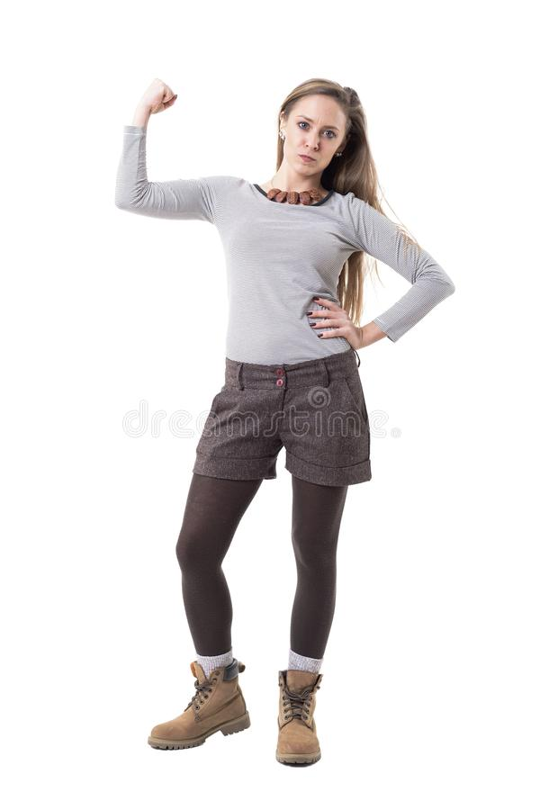 Confident tough strong cute hipster girl flexing biceps arm muscles. stock image