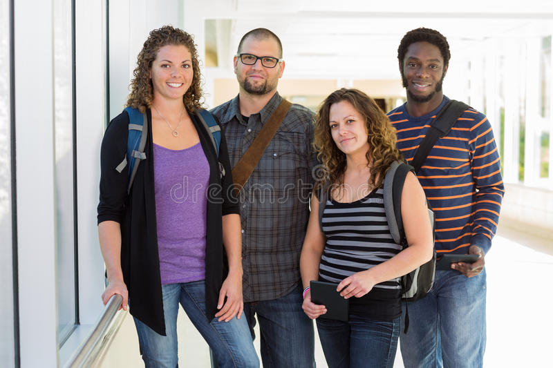 Confident University Students Standing At Corridor stock photos