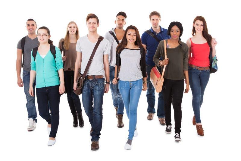 Confident university students walking over white background stock photo