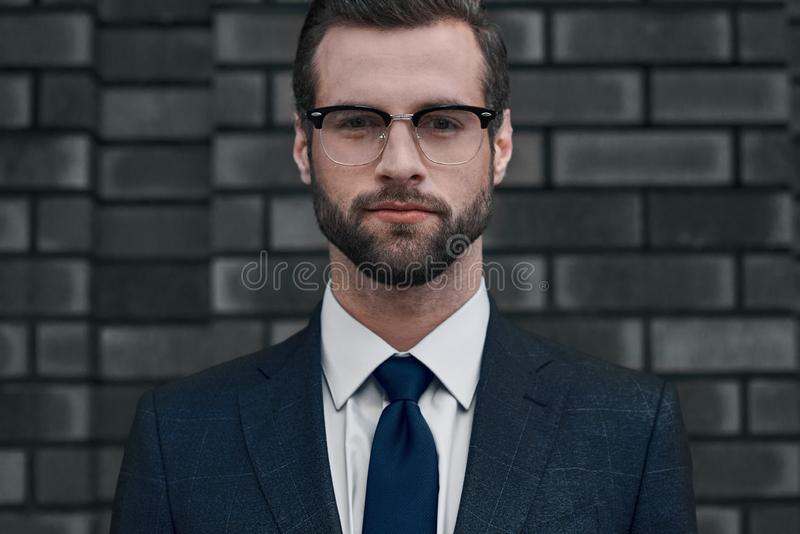 A confident view of the leader. A young businessman in glasses and with a beard looks directly at you stock photos