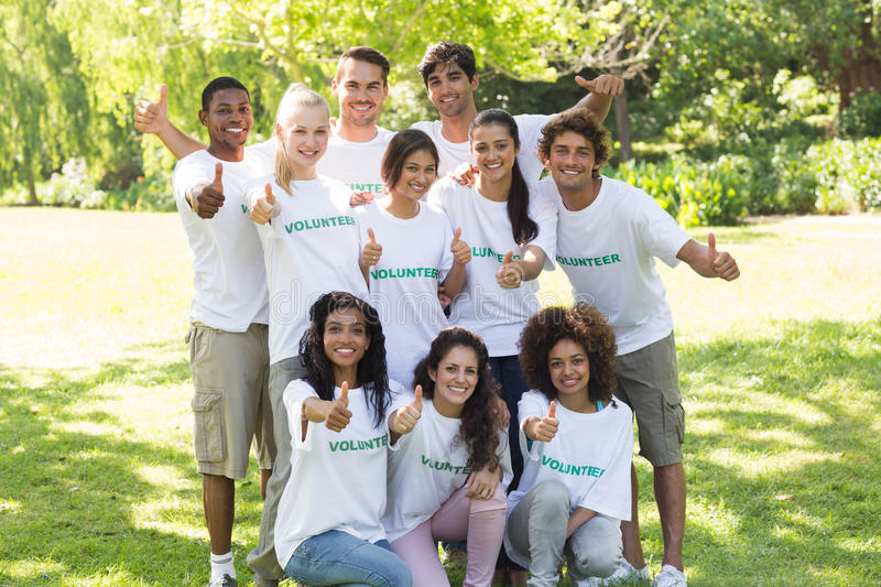 Confident volunteers raising thumbs up royalty free stock photography