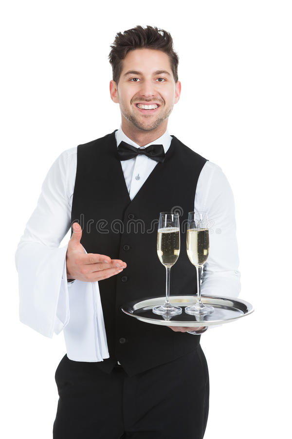 Confident Waiter Carrying Champagne Flutes On Tray stock photo