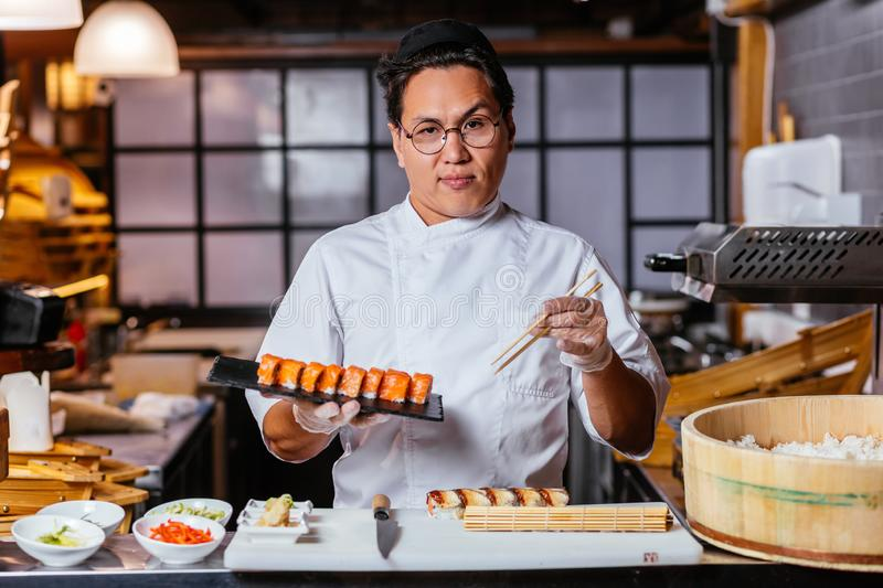 Confident waiter with a plate of sushi set. Close up photo royalty free stock images