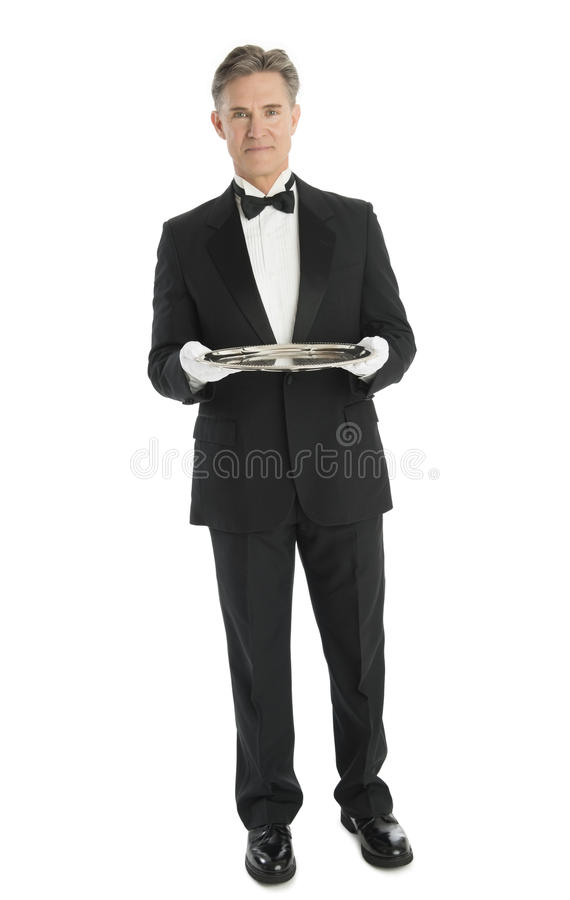 Confident Waiter With Serving Tray Standing Against White Background stock photo