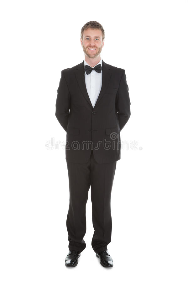 Confident waiter standing hands behind back royalty free stock photo