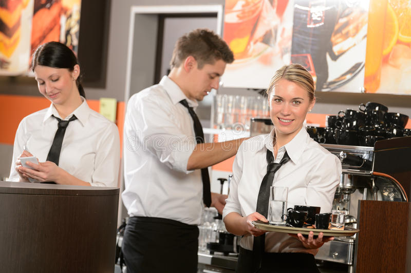 Confident waitresses and waiter working in bar royalty free stock images