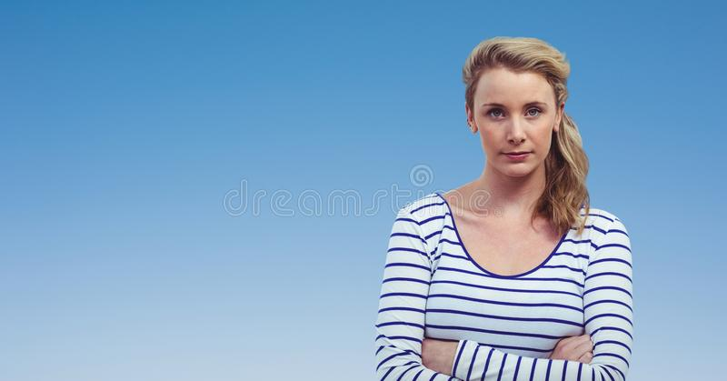 Confident woman with arms crossed against clear blue sky royalty free stock image