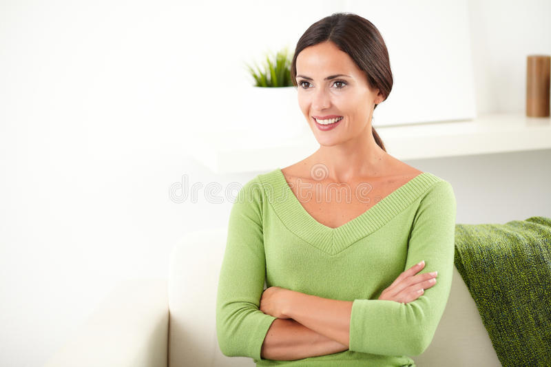 Confident woman with arms crossed looking away. Confident young caucasian woman with arms crossed looking away and smiling at indoors - copy space stock photos