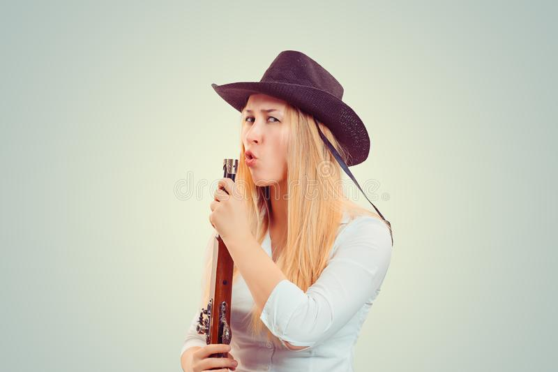 Confident woman blowing at gun after shooting. Modern blond woman in cowboy hat holding gun and blowing at it after shooting royalty free stock photos