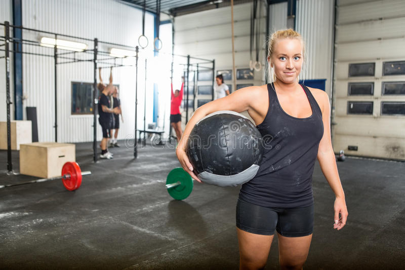 Confident Woman Carrying Medicine Ball. Portrait of confident women carrying medicine ball in gym stock images