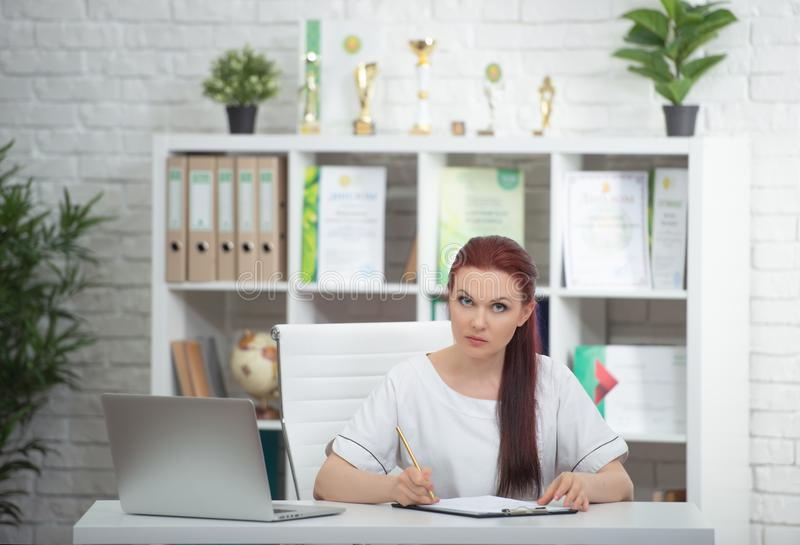 Confident woman doctor sitting at the table in her office and smiling at camera. healthcare concept stock photography