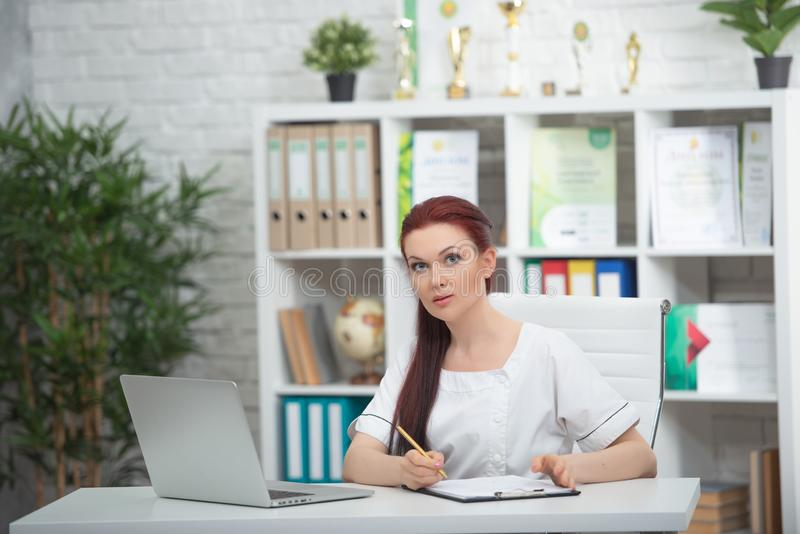 Confident woman doctor sitting at the table in her office and smiling at camera. healthcare concept royalty free stock images