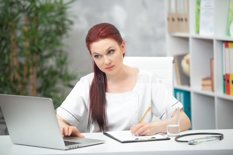 Confident woman doctor sitting at the table in her office and works at the computer. healthcare concept stock images