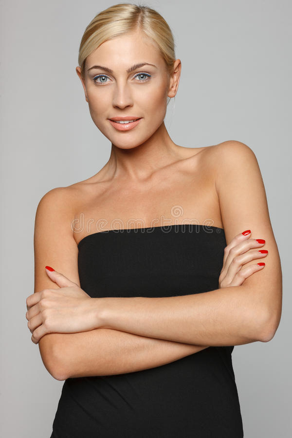 Confident woman with folded hands. Beautiful blond woman smiling at the camera with folded arms wearing black top over gray background stock images