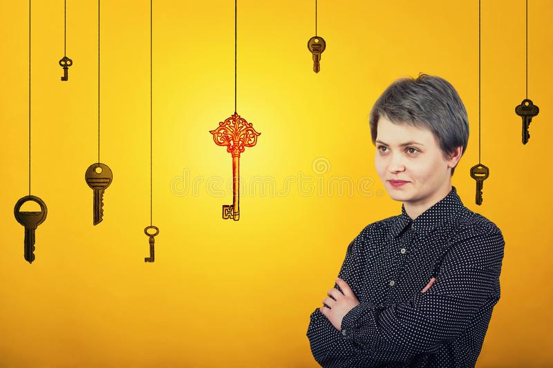 Confident woman keeps hands crossed, looking aside with a positive smile. Satisfied female find the magic golden key. Aspirations royalty free stock image