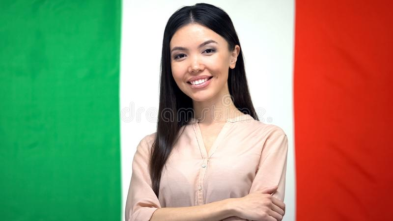 Confident woman looking at camera against Italian flag background, citizenship royalty free stock photos