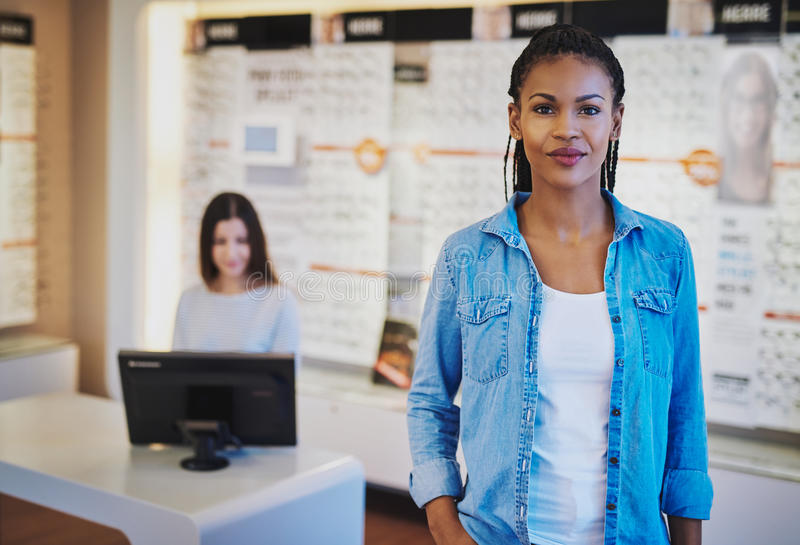 Confident woman opening her own store. Confident women opening her own store, looking relaxed with colleague in background stock photos