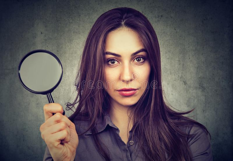 Confident woman posing with magnifier royalty free stock photography