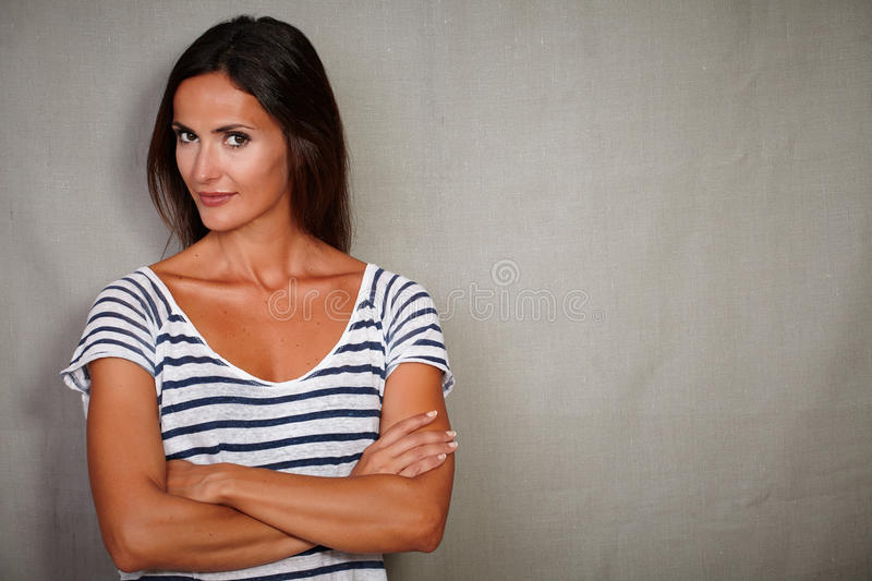 Confident woman standing with arms crossed stock image
