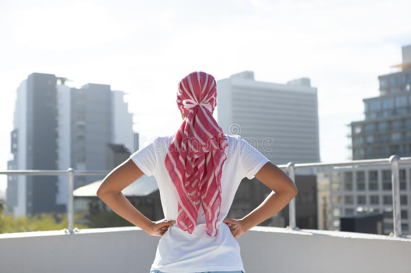 Confident woman standing in city for breast cancer awareness stock photography