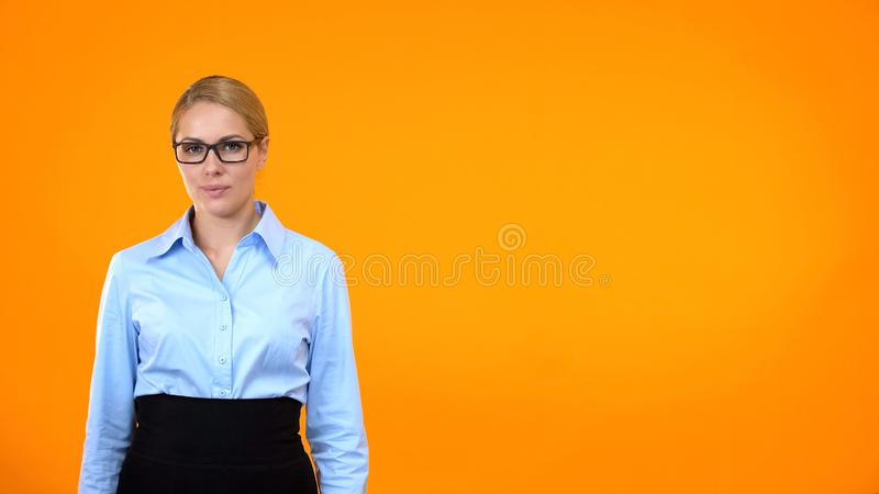 Confident woman in suit and eyeglasses on orange background, business coach royalty free stock photography