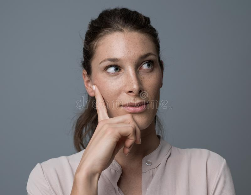 Confident woman thinking with hand on chin stock photos