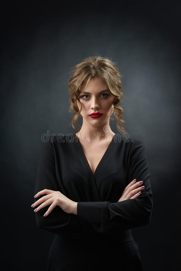 Confident woman wearing red lipstick posing in front of camera. Confident woman wearing red lipstick and stylish black dress is posing in front of camera on stock images