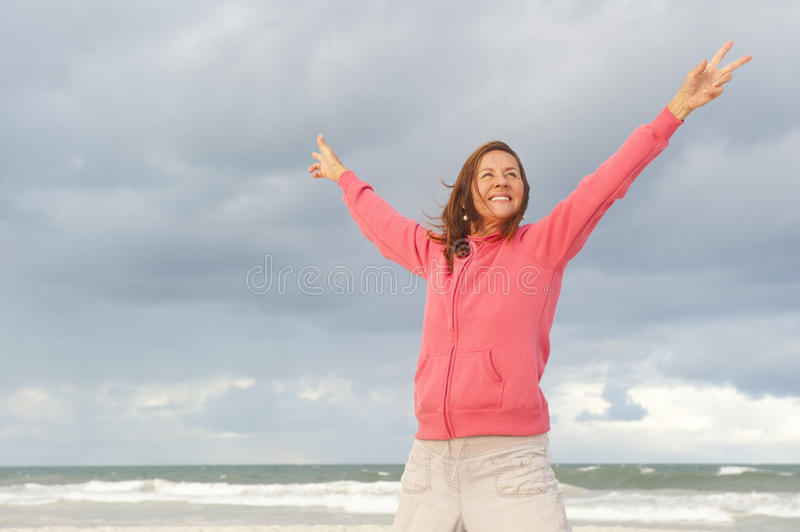Confident woman in winning pose at ocean. An attractive looking mature woman in her fifties in a winning pose at the beach, with her hands up in the air, wearing royalty free stock photography