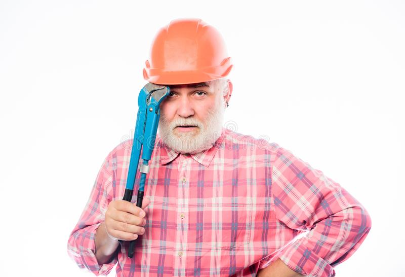 Confident worker. man builder with adjustable pipe wrench. build and construction. professional repairman in helmet with stock image