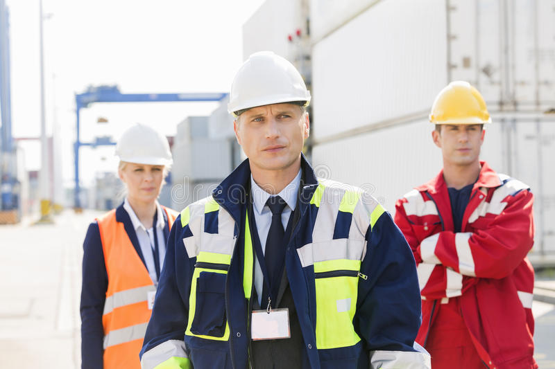 Confident workers standing in shipping yard stock image