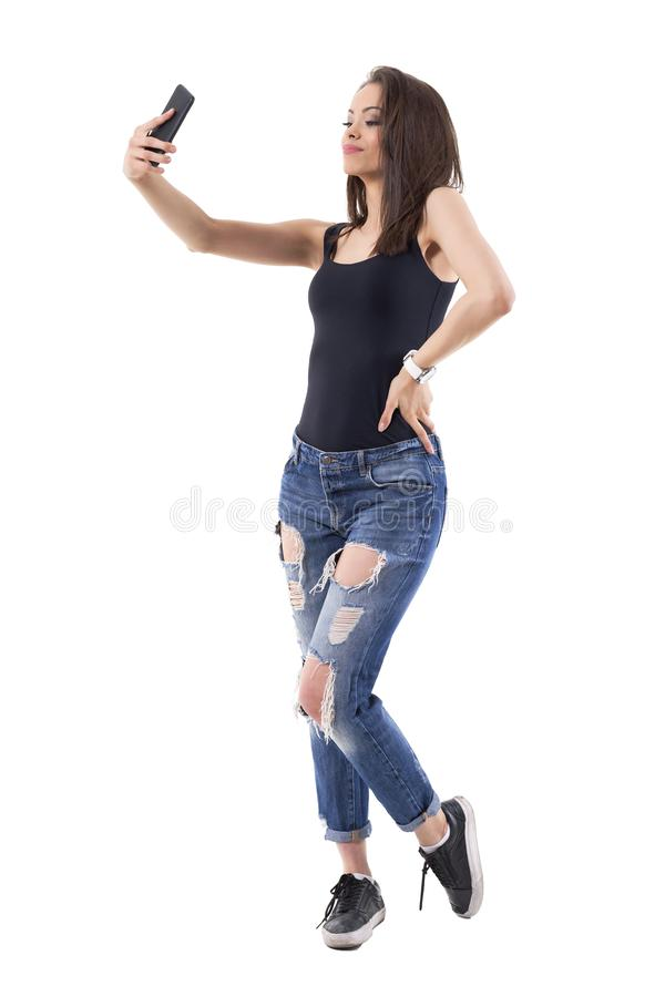 Confident young adult passionate woman taking selfie photos with mobile phone. royalty free stock photo