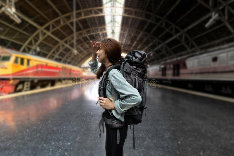 Confident young Asian backpacker woman looking new challenges at train station. Summer travel vacations lifestyles stock photography