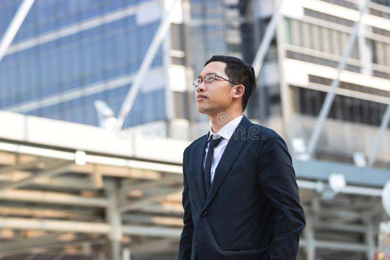 Confident young Asian business man in suit standing and looking at far away at outside office stock photos