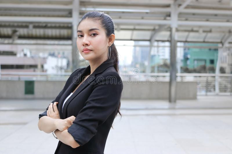 Confident young Asian business woman crossing one`s arms at outside office stock photography