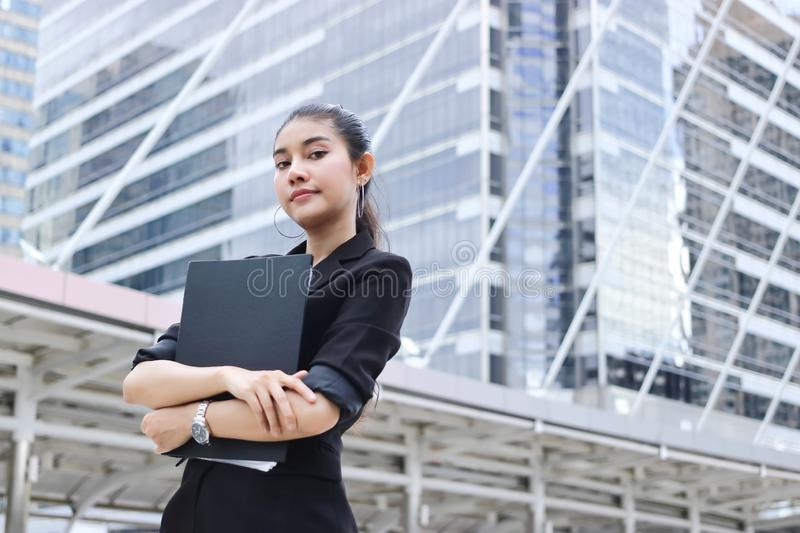 Confident young Asian business woman with document folder standing at outside office. Confident young Asian business woman with document folder standing at stock photos