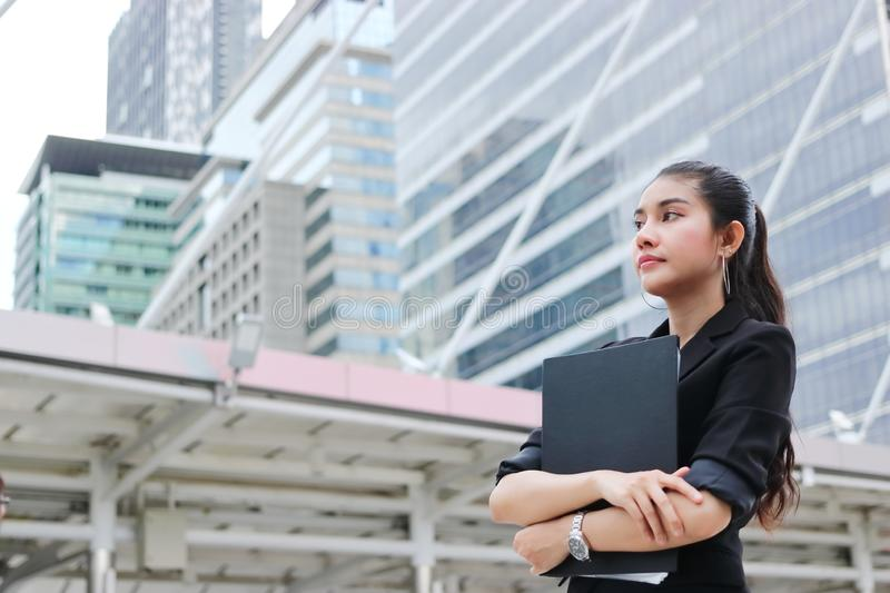 Confident young Asian business woman with document folder standing at outside office royalty free stock photos