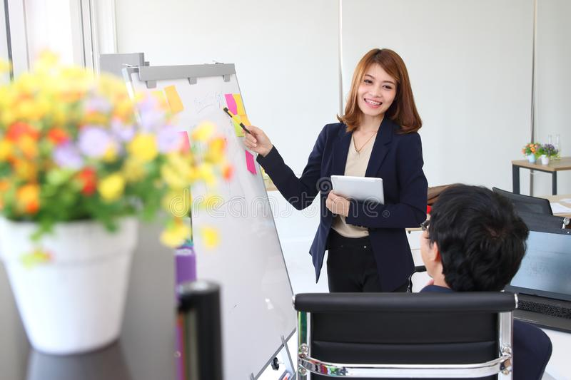 Confident young Asian business woman explaining strategies on flip chart to executive in boardroom royalty free stock images